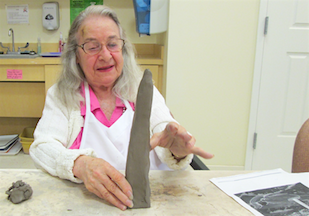 resident forming the Washington Monument in clay