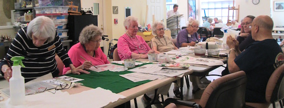 residents and an instructor working with ink brushes