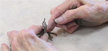 hands creating a clay tree